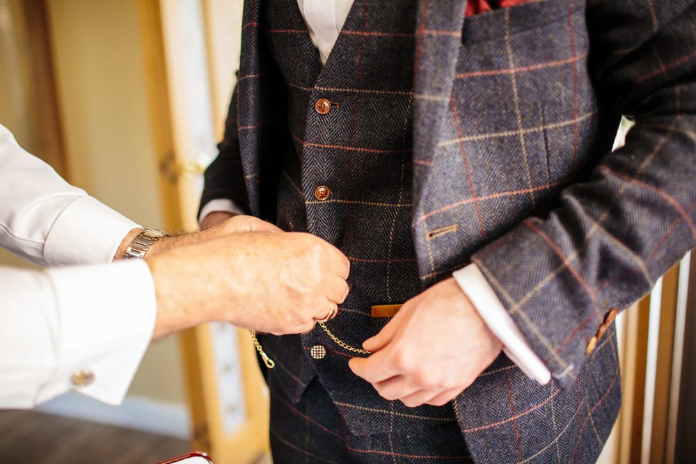 Groom attaching his pocket watch