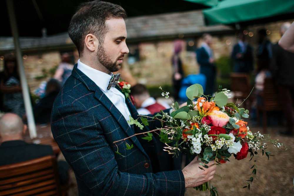 Groom holds the brides bouquet at their wedding