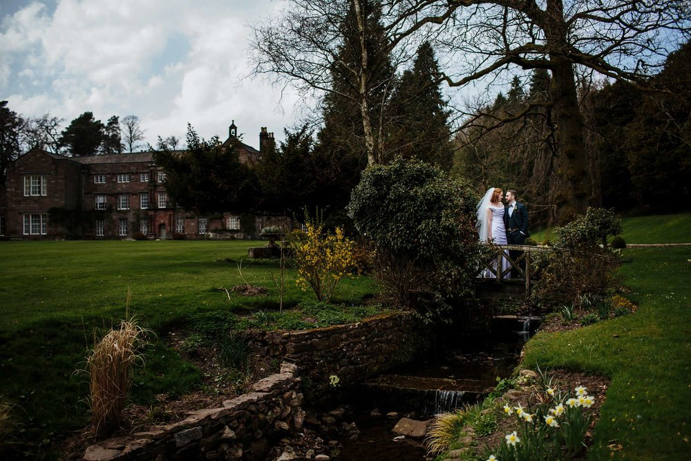 Bride and groom standing on a bridge in the gardens of Browsholme Hall Wedding