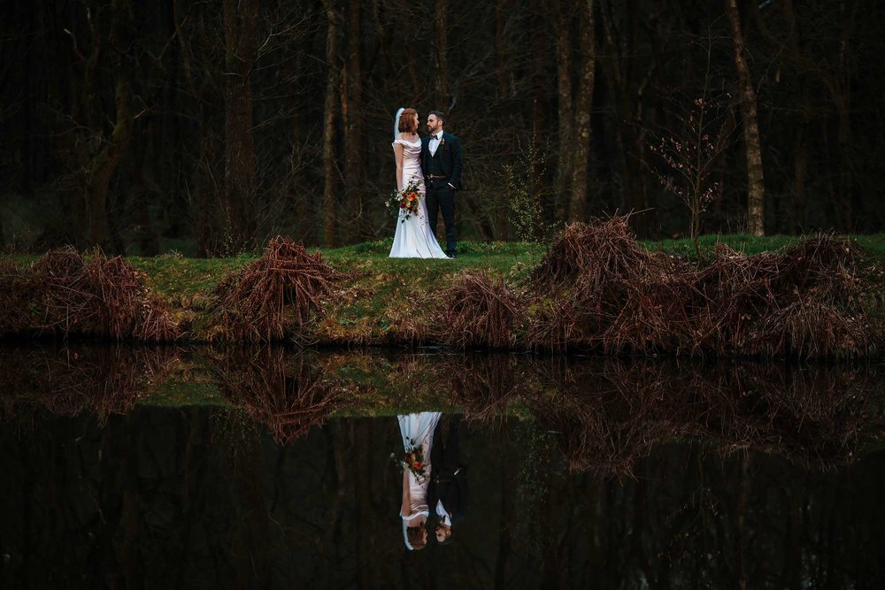 Bride and groom pose by the lake at their wedding