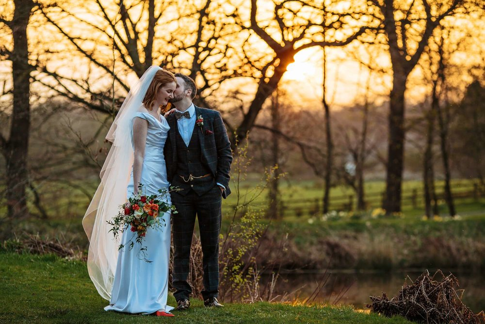 Groom kisses his bride at sunset at their Browsholme Hall Wedding