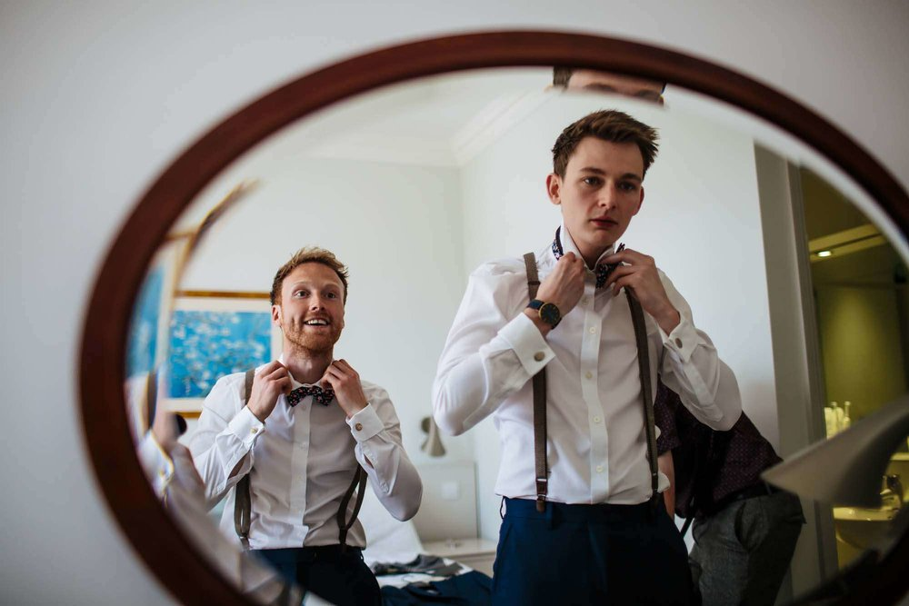 Groom putting his bow tie on in the Lake District