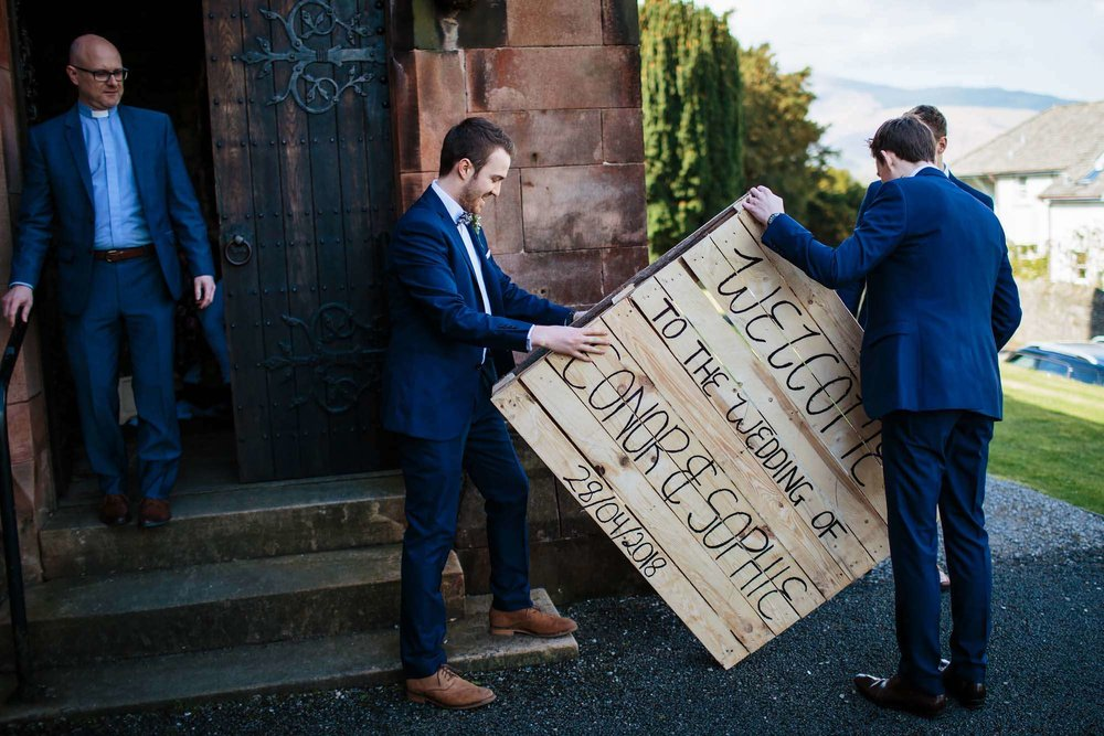 Erecting the wedding sign as vicar looks on