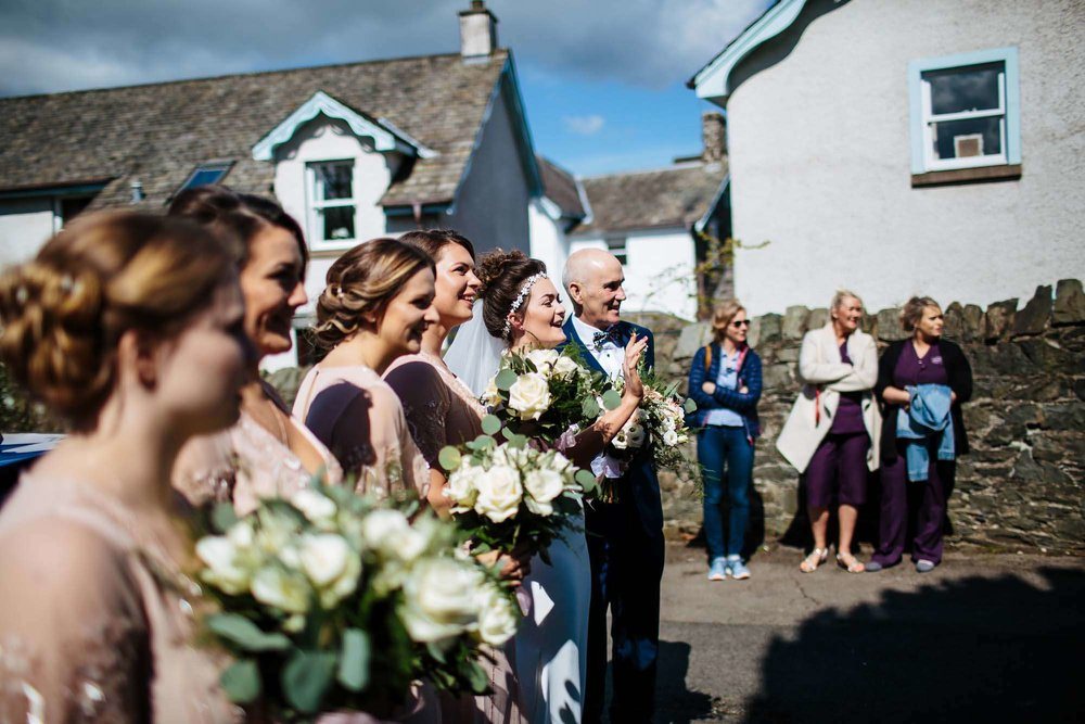 Bride and bridesmaids at a sunny Lake District wedding