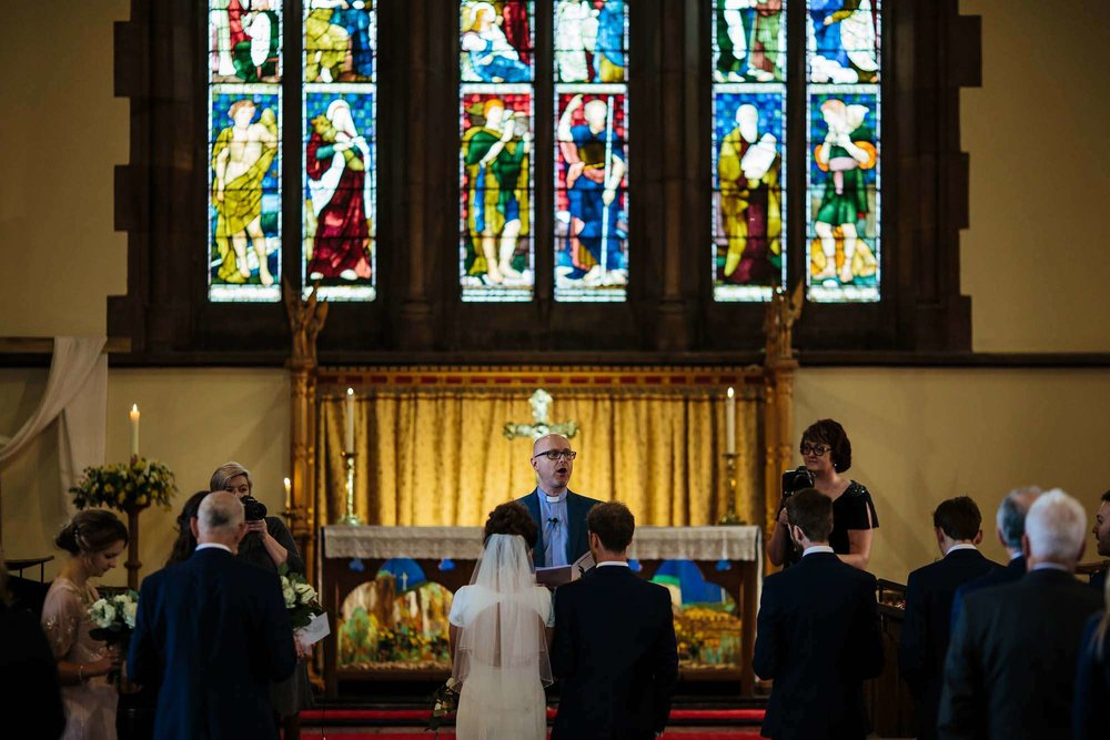 The vicar addressing the bride and groom at their wedding