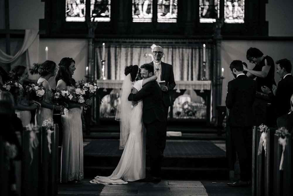 Bride and groom hugging at the altar in church