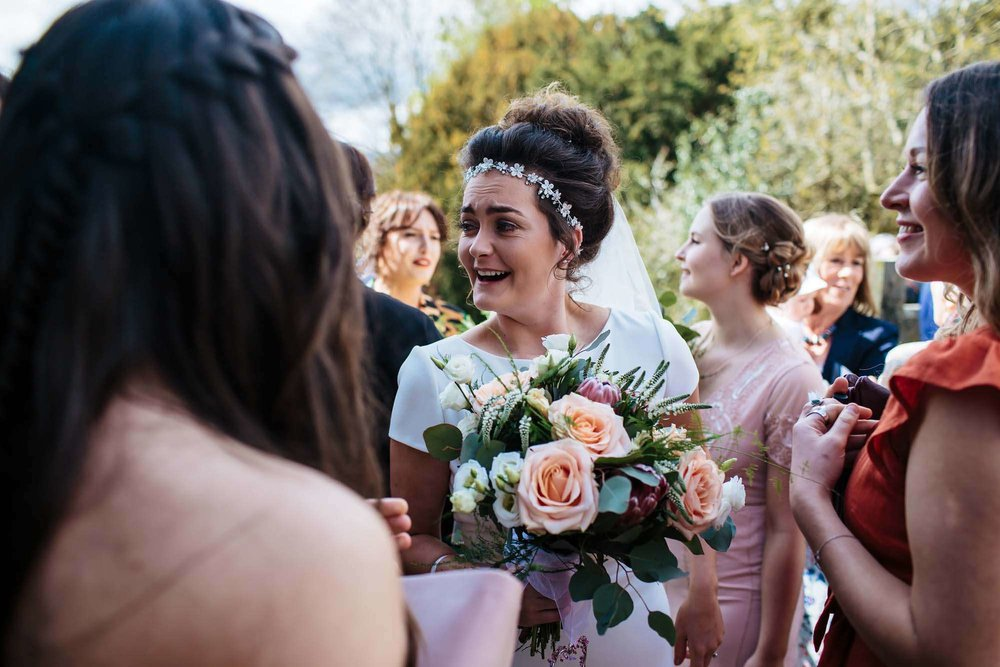 Bride laughing with guests at her wedding in Keswick
