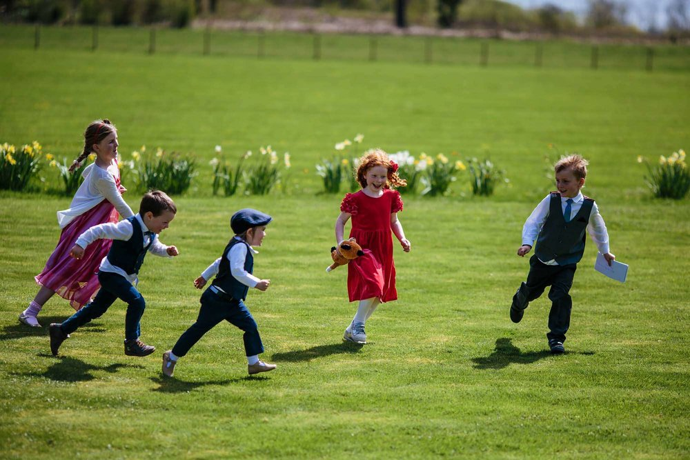 Children playing on the grass at a wedding at Armathwaite Hall