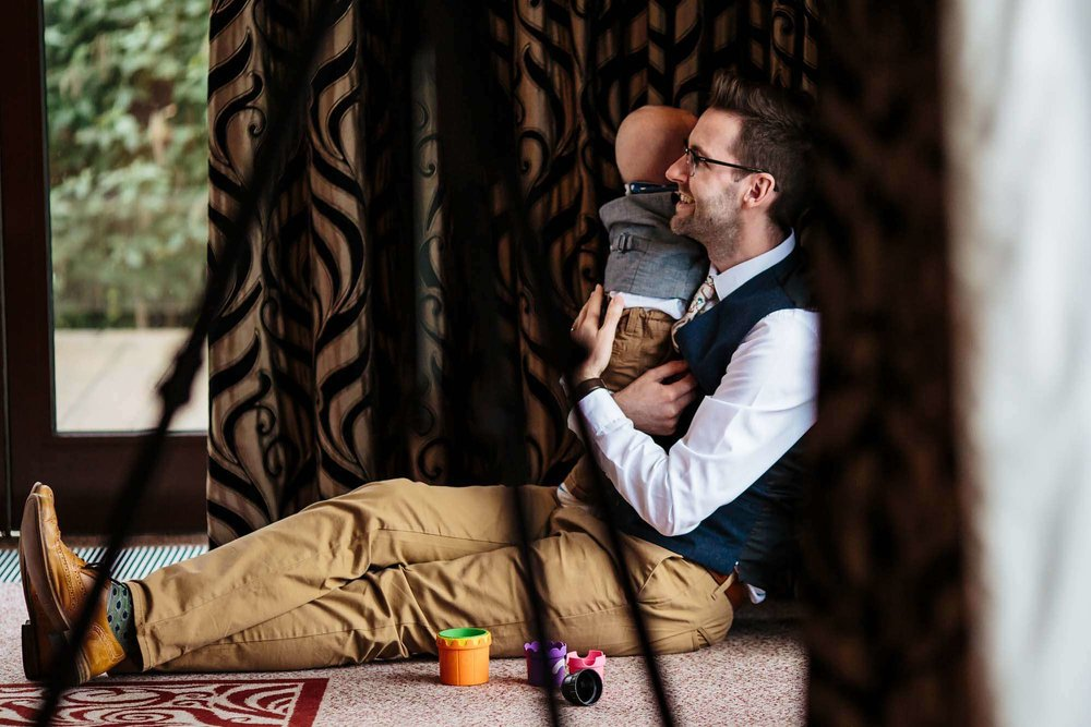 Wedding guest with small child sitting on the floor during the speeches