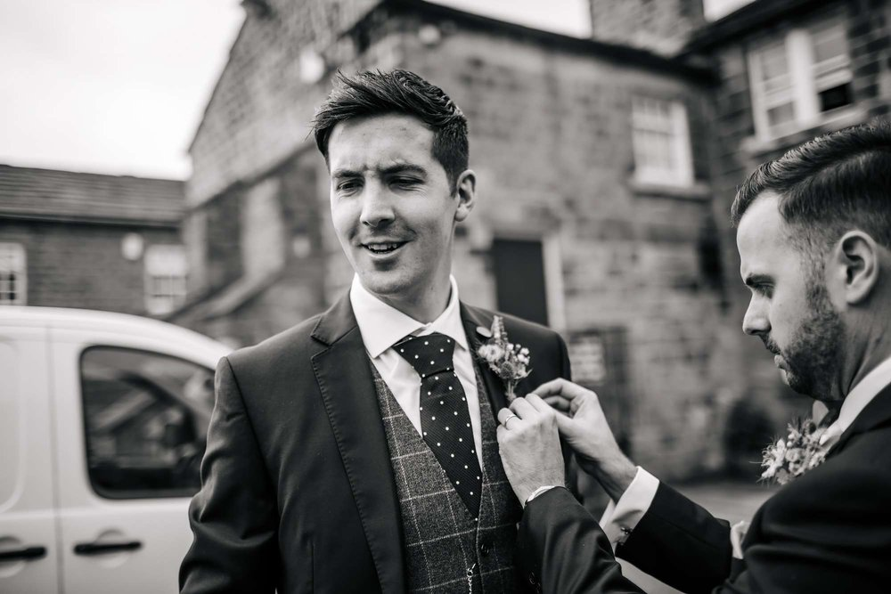 Groom having his buttonhole inserted at his wedding