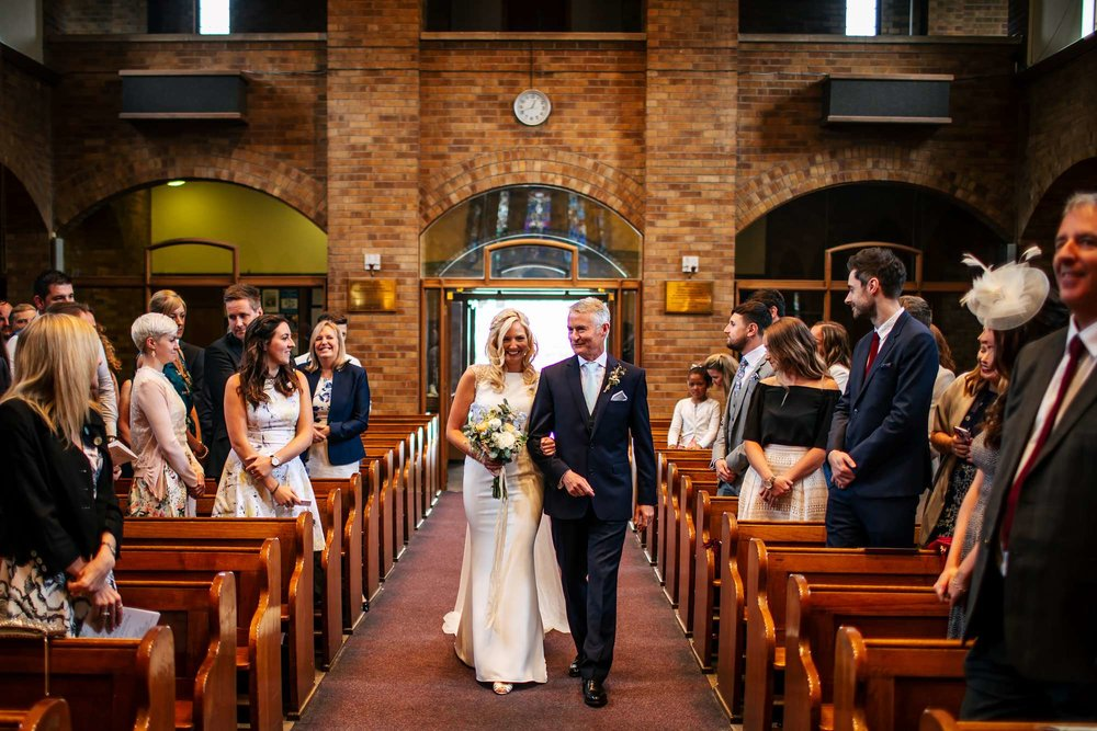 Bride and dad walk down the aisle at a Leeds wedding