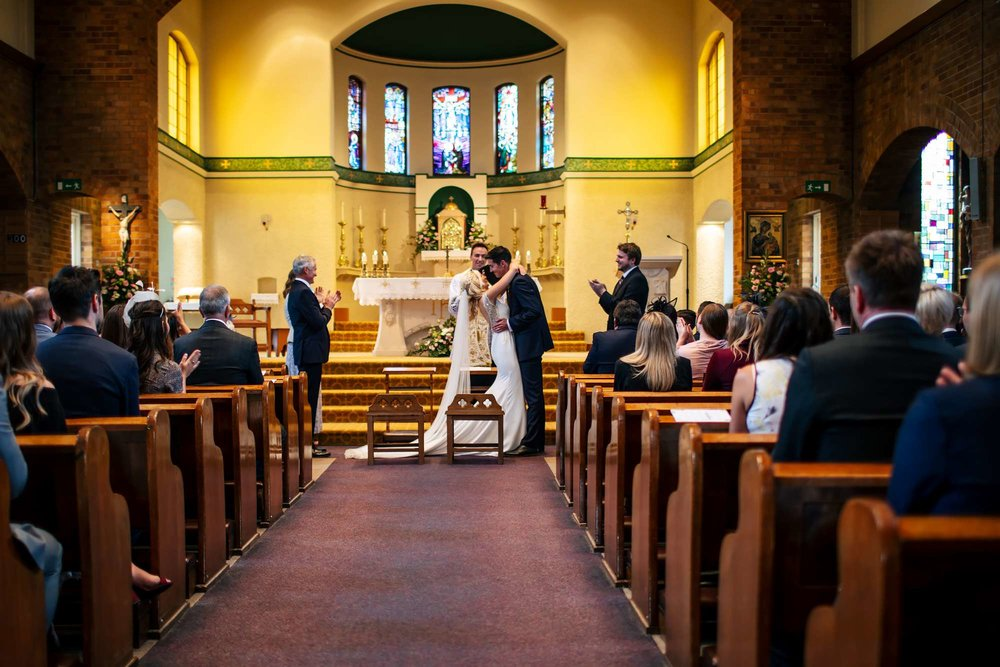 A first kiss as man and wife at a church wedding
