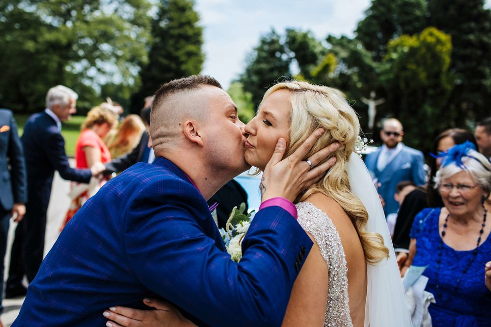Guests kiss the bride outside her church wedding