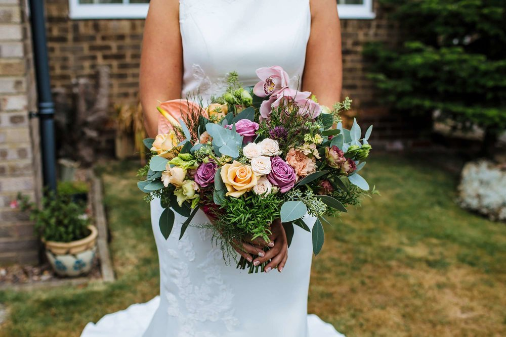Bride holds her bouquet at her wedding