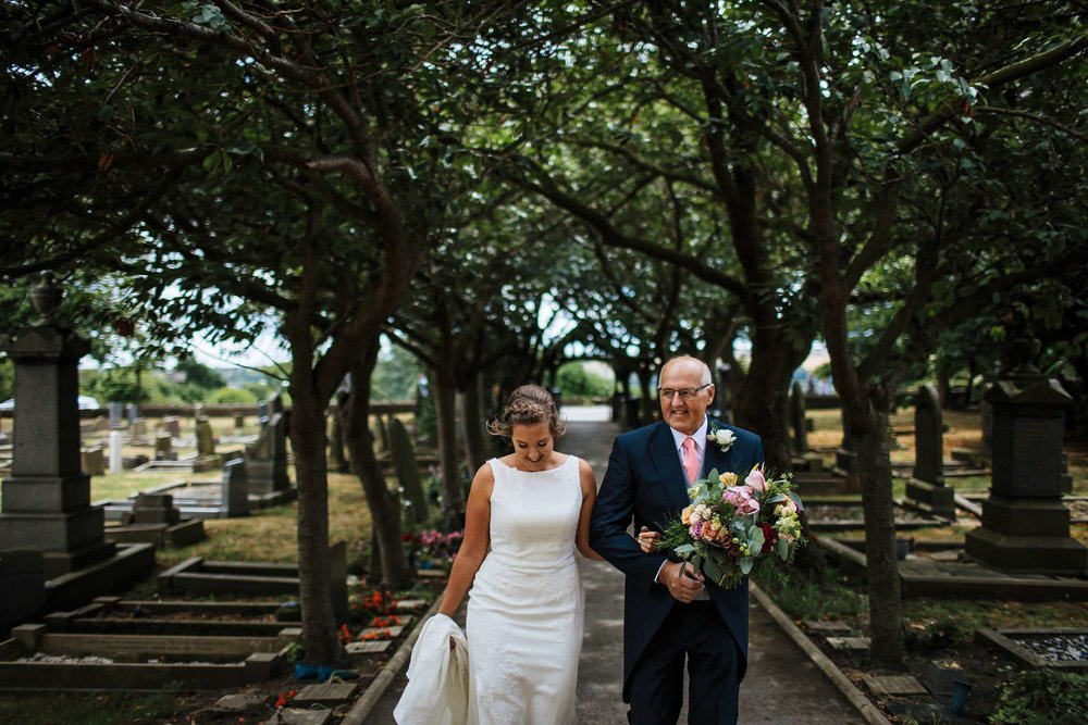 Bride and father walking to the church on her wedding day