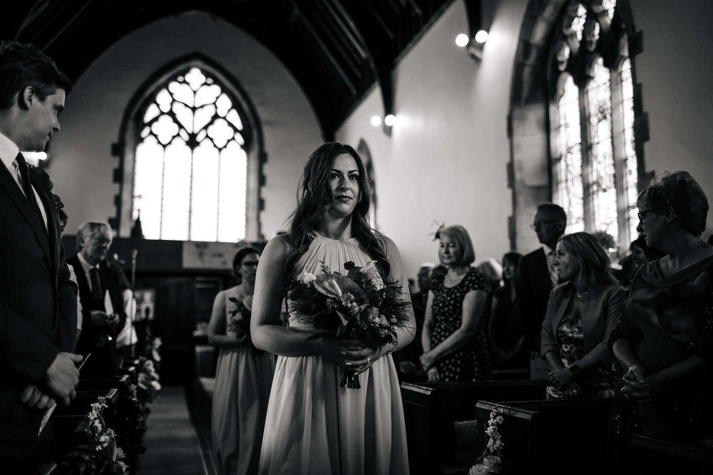 Bridesmaid walking down the church aisle