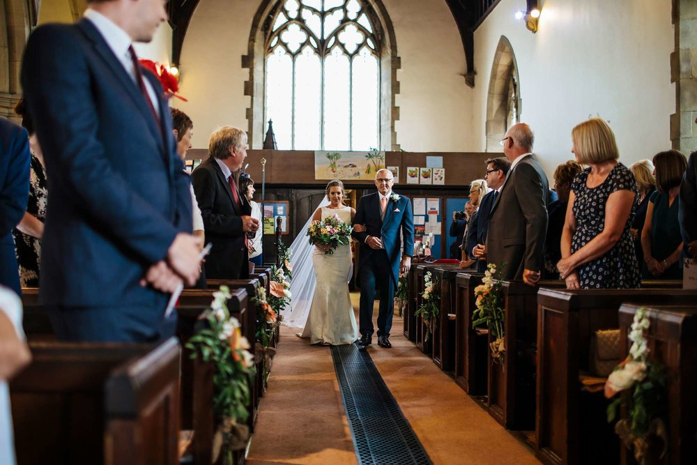 Bride and father walking down the aisle at a wedding