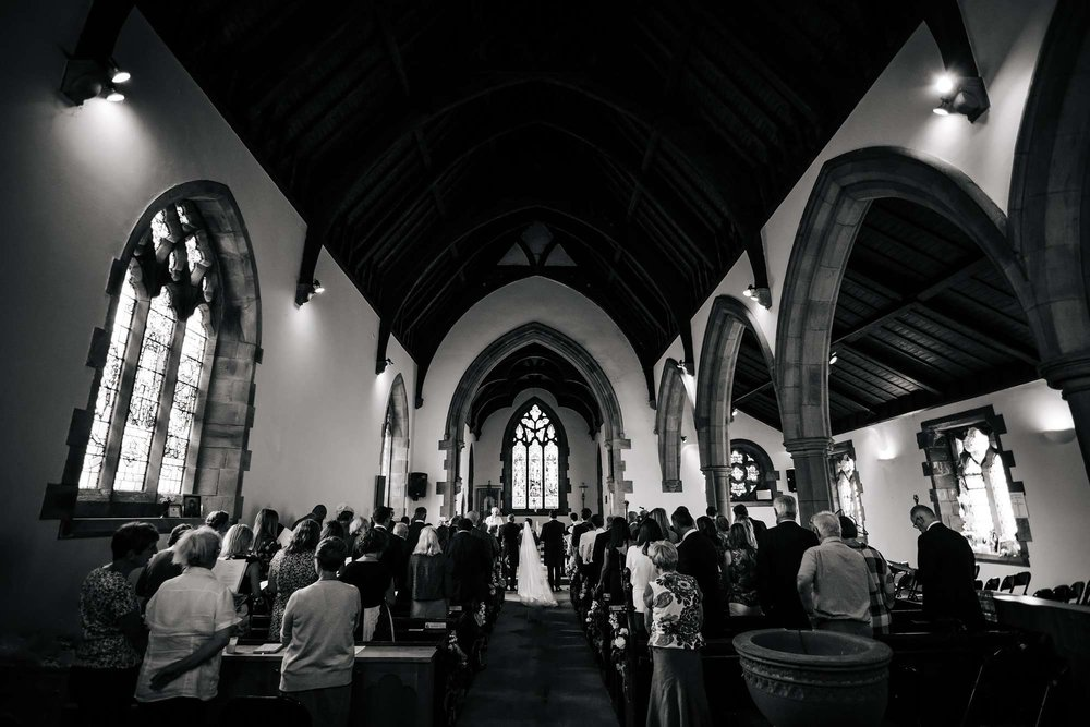 Black and white wide shot of the church interior of a wedding