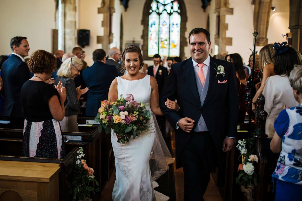 Bride and groom smiling as they walk down the aisle