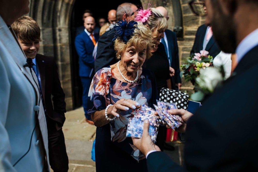 Wedding guest taking confetti in the sunshine