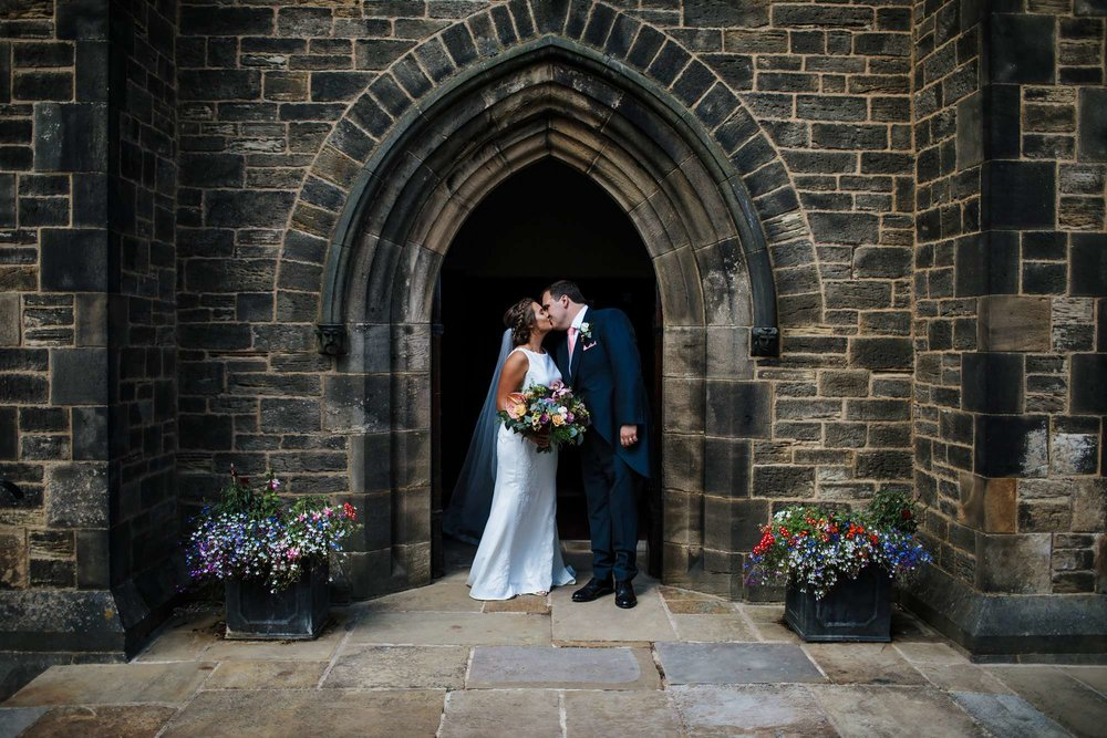 Bride and groom kissing outside a church in Huddersfield