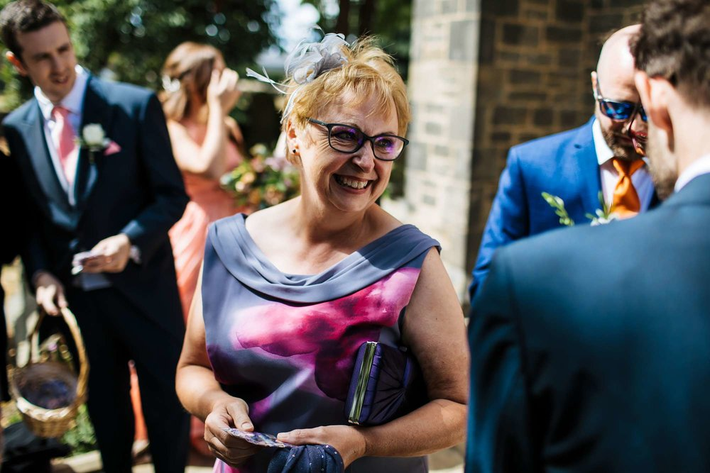 Wedding guests laughing in the sunshine in Yorkshire