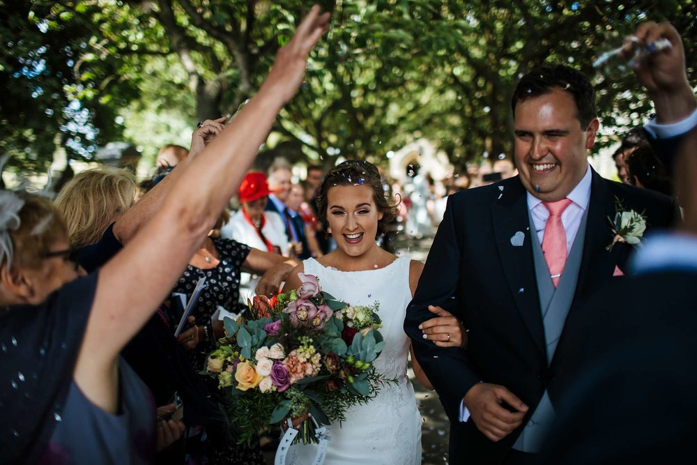 Bride and groom under the confetti line on their wedding day