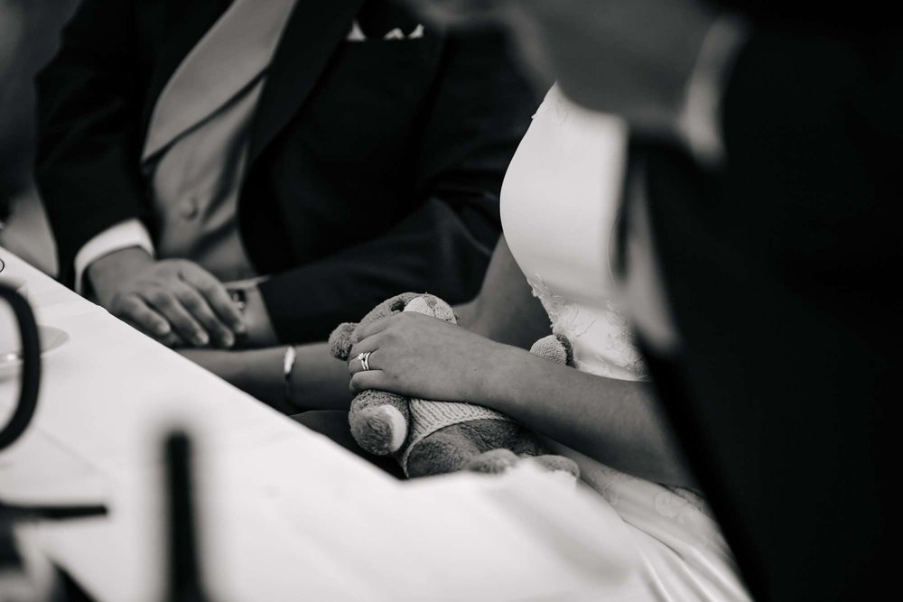 Detail of the bride holding her teddy during the wedding speeches