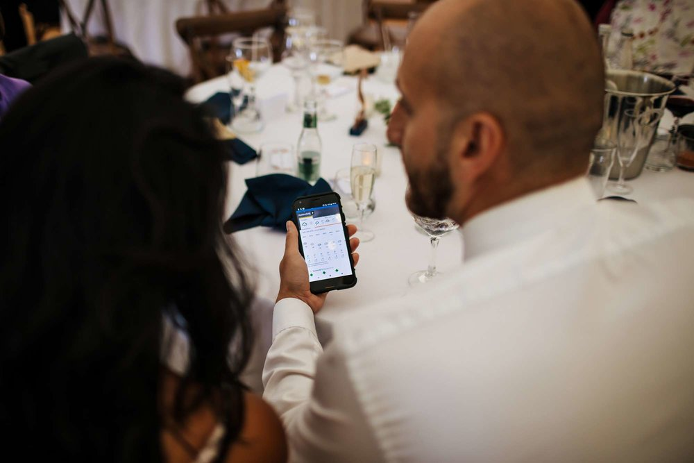 Wedding guests checking the weather forecast on a phone
