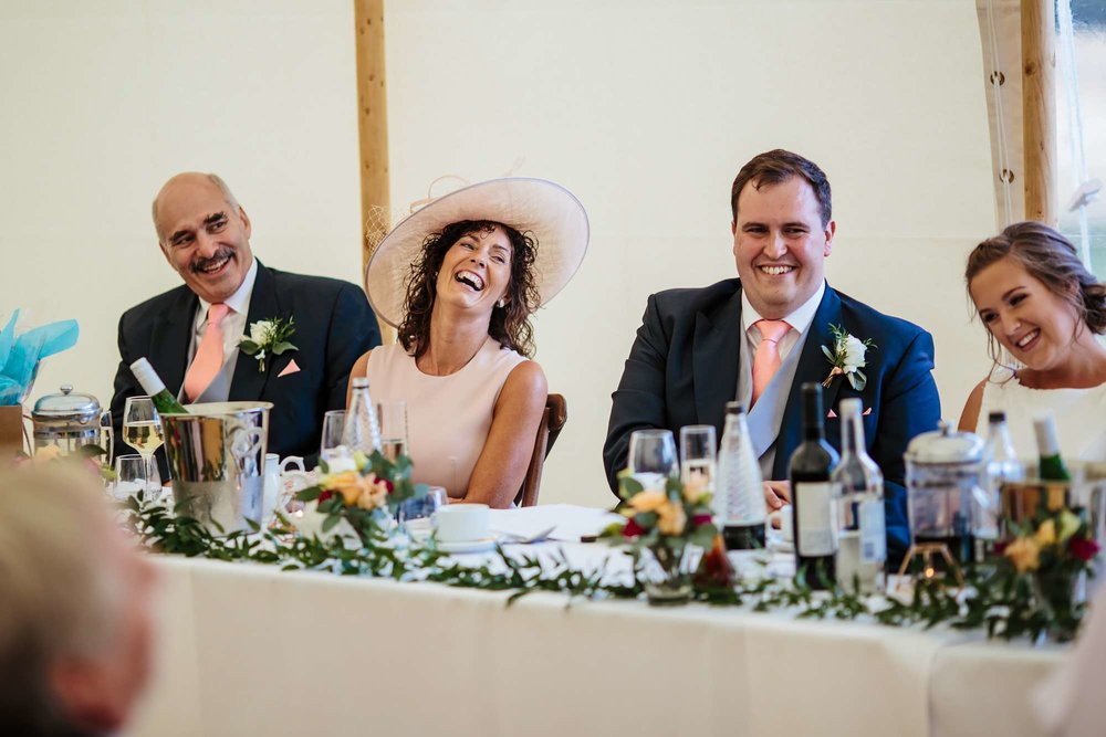 Groom and his mum laughing during his wedding speeches