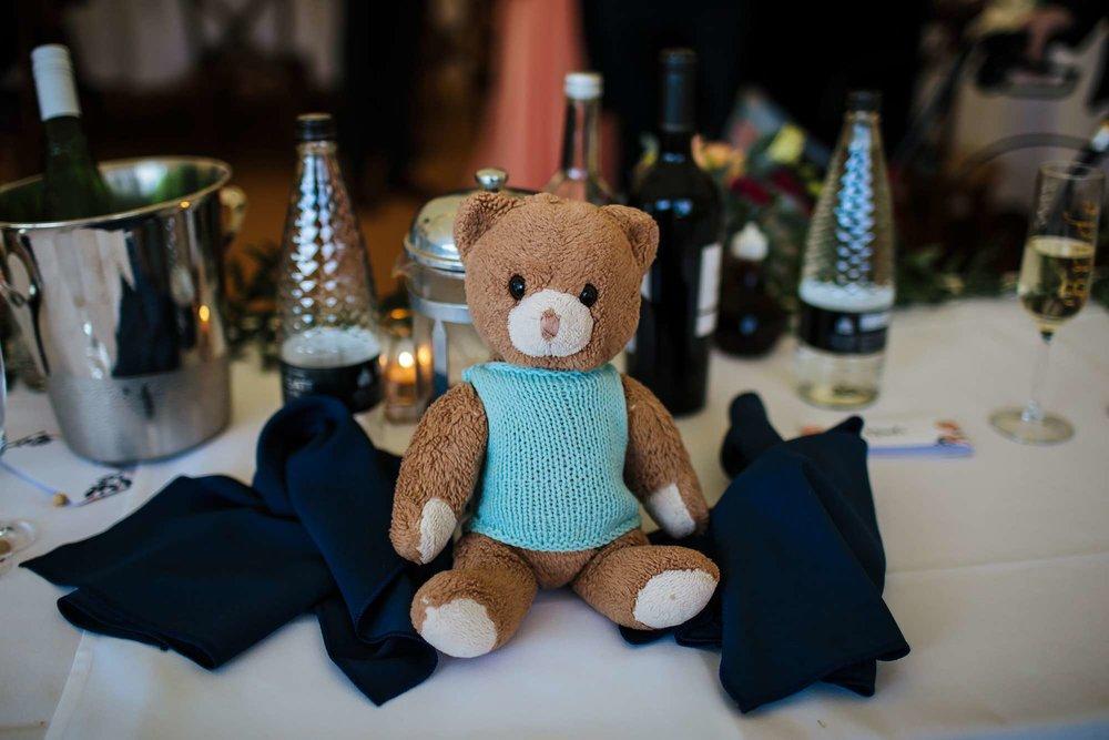 Teddy bear sitting on the table at a wedding