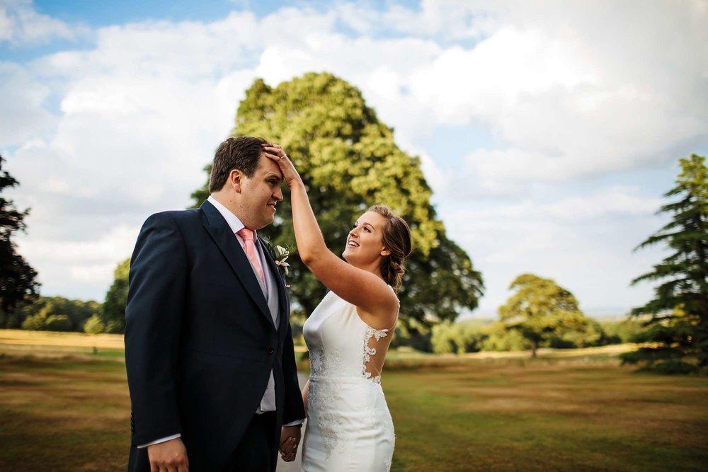 Bride adjusting the groom's hair at a Yorkshire wedding