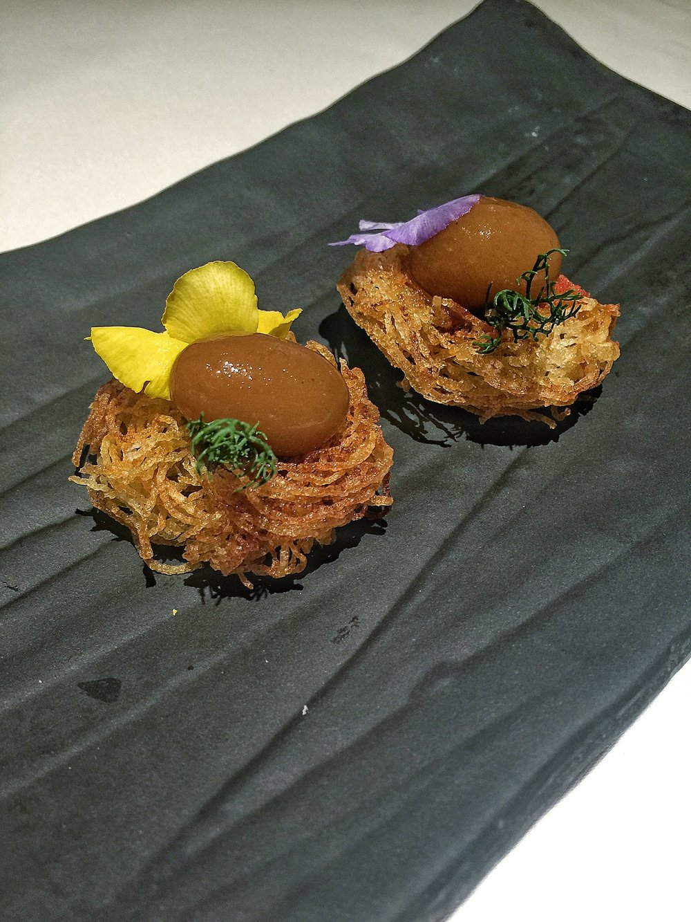 Gaggan's take on the popular Parsi dish of meat curry with potato sticks (Salli Boti) represented with a lamb curry chutney sphere sitting atop a fried potato nest.