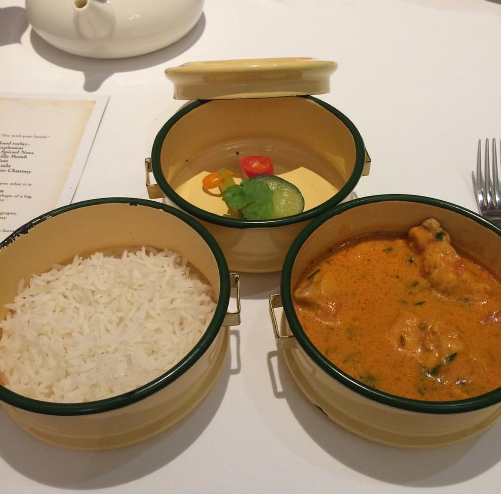Chicken tikka masala served with naan, rice and pickled veg in a tiffin box.