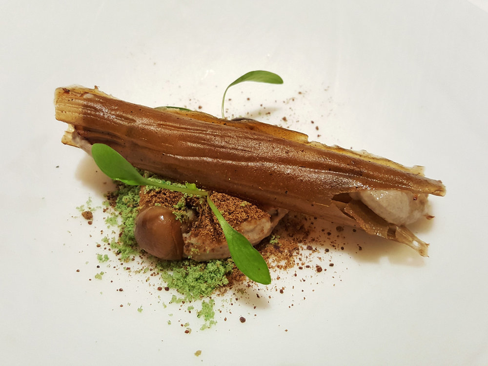 The magic mushroom - Forest mushrooms made of black and white truffles in the form of a mousse stuffed into a crispy round, shaped in a log, edible mushroom soil and the garden represented by green chilli powder.