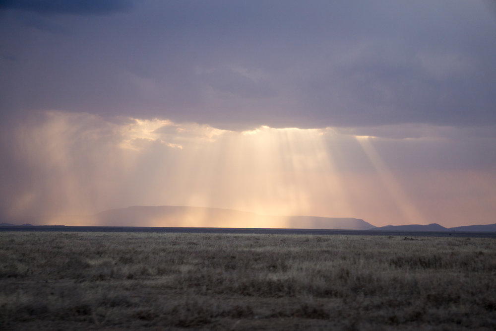 Rain and sun rays across the savannah.