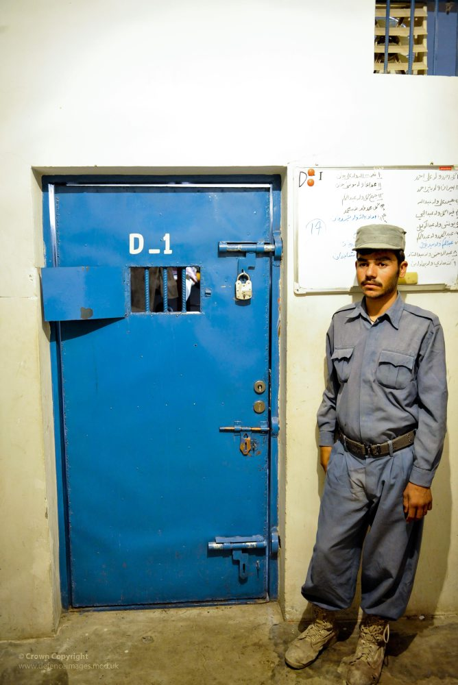 An Afgan Policemean guards a solitary confinement cell in the Lashkar Gah Central Prison in Helmand Province. Credit: UK Ministry of Defence