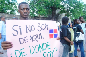 "A young man in the Dominican Republic with a sign that reads ""If I'm not from here, then where am I from?"" Source:  Impacto Latin News ."