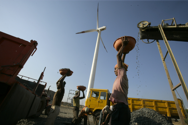 A laborer is seen working at a diesel powered crusher in font of a wind turbine. Photo Credit: Land Rover Our Planet