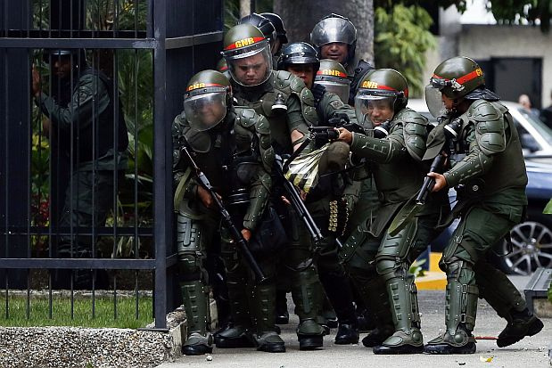 National Guard members respond to anti-government protests in Venezuela. An OAS report in 2018 denounced crimes against humanity occurring in Venezuela. Image Source:    MARQUINAM   , Flickr (   CC BY-NC-ND 2.0   ).