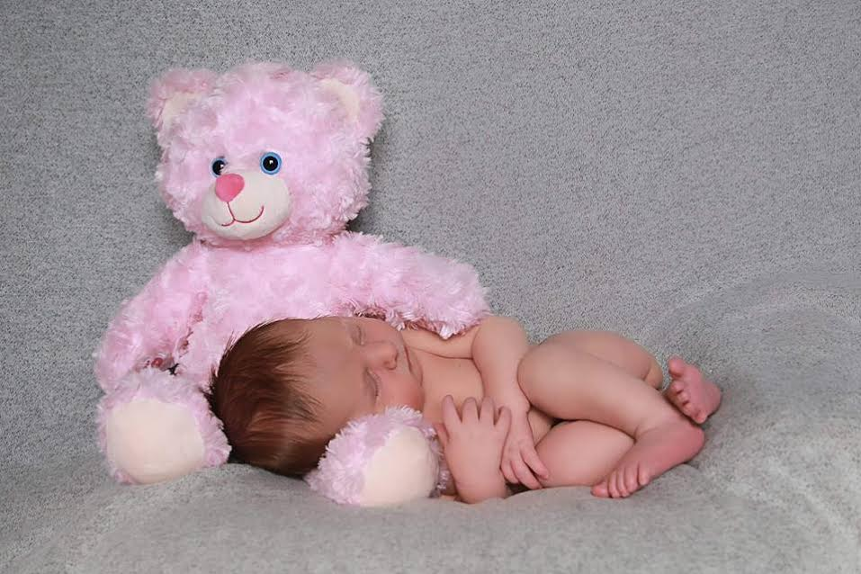 Their sweet rainbow baby, cuddled close with Riley Bear