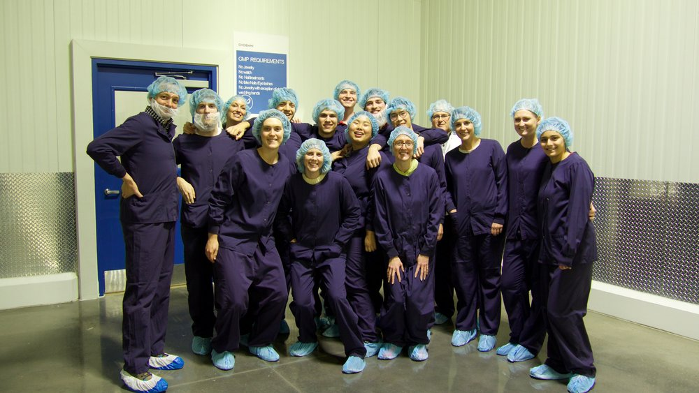 group photo of factory tour attendees dressed in scrubs