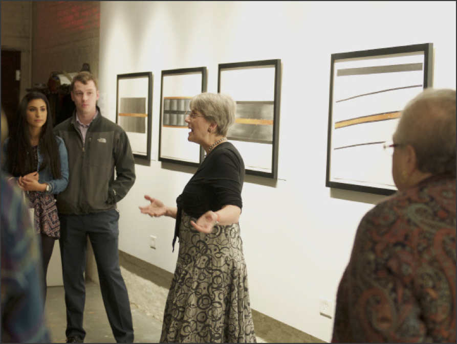Lindsay Olson, the resident artist at Fermilab, explains her artwork to guests at a reception held in the Accelerator Art Space on Tuesday, March 7. Photo by Lauren Vana