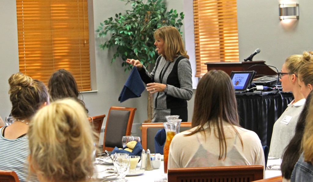 Patricia Cook, a professional business consultant, explains the etiquette behind proper napkin use to students during an interactive din- ner on Wednesday, Oct. 5. (Photo by Annie Williams)