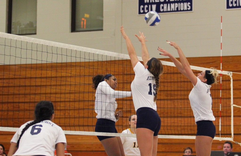 Sophomore Alyssa Olsen jumps to defend an attempted spike against Augustana on Tuesday Oct. 4 (Photo by Kivin Woods)