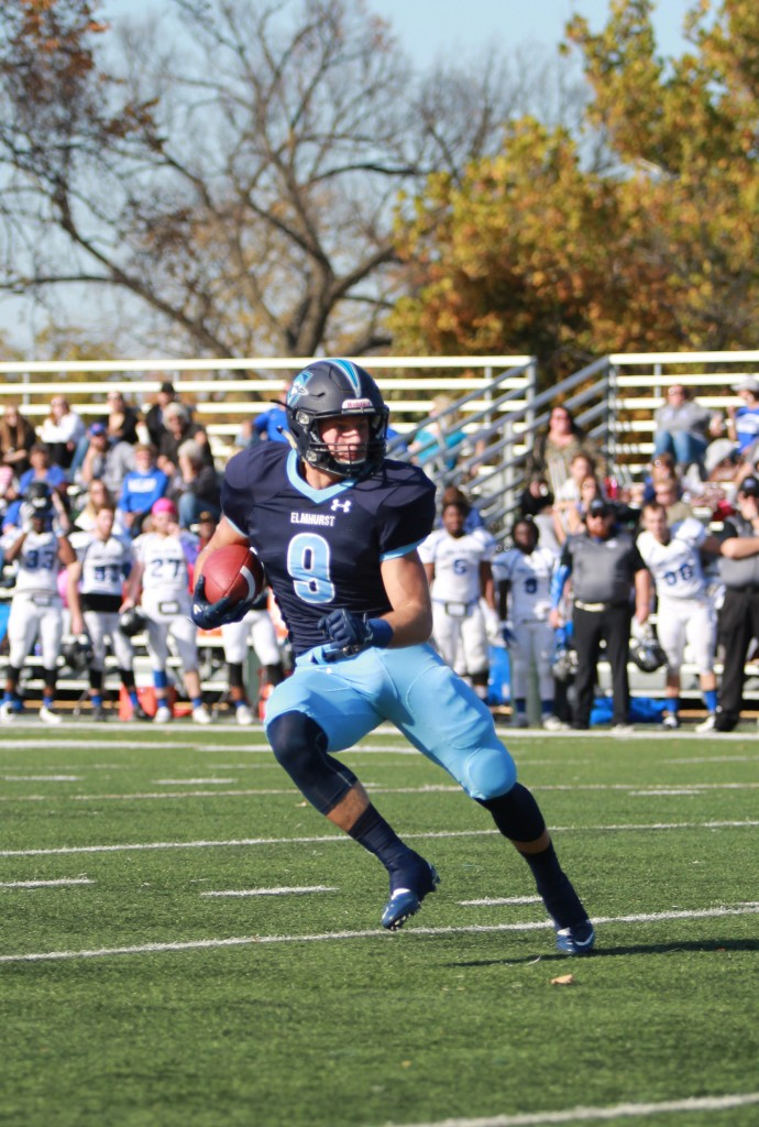 Junior Tyler Hosman runs the ball upfield and prepares to juke a Millikin tackle on Saturday, Nov 5. (Photo by Kivin Woods)