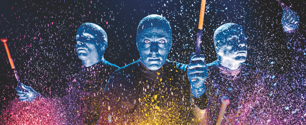 "The blue men play drums as colorful paint splashes around them during a ""Blue Man Group"" performance at the Briar Street Theater in Chicago, Illinois. (Photo courtesy of Blue Man Group)"