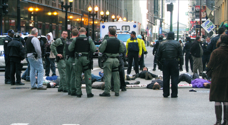 Students stage a Die-In, an act of non-violent protest in which demonstrators pretend to be dead, to fight for free tuition in the streets of downtown Chicago on Monday, Oct. 24. (Internet Photo)