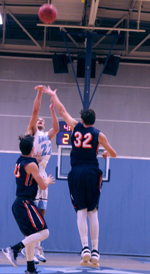 Senior forward Caleb Mowry shoots over two Wheaton defenders on Saturday, Dec. 3. (Photo by Kivin Woods)