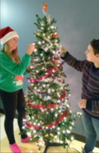 EC students Jessie Allcock and Taylor Dorband decorate the student lounge in West Hall with a Christmas tree. (Photo courtesy of Jessie Allcock)